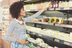 Приятная молодая женщина делает приобретения в органическом магазине Стоковые Изображения RF