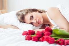 Приятная очаровательная девушка лежа в кровати Стоковые Фотографии RF