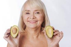 Приятная очаровательная женщина имея 2 половины авокадоа в ее руках Стоковая Фотография