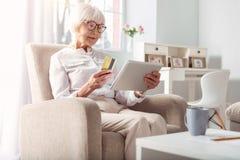 Приятная пожилая женщина делая онлайн ходить по магазинам дома Стоковое Изображение RF