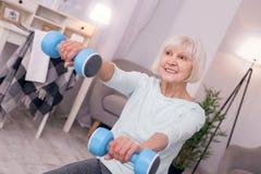 Приятная пожилая женщина держа голубые гантели и усмехаться Стоковые Изображения