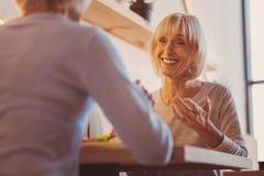 Приятная старшая женщина разговаривая с ее другом в ресторане Стоковое Изображение