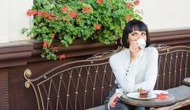 Приятные время и релаксация Брюнет стороны макияжа женщины мечтательный ест предпосылку террасы кафа торта гастрономическо стоковое изображение