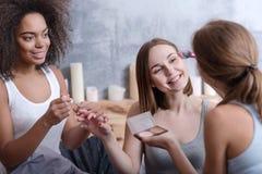 Приятные девушки помогая ее другу получая готовый дома Стоковое Фото