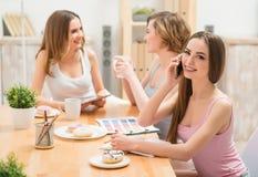 Приятные девушки сидя на таблице Стоковое Фото