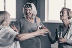 Приятные старшие женщины общаясь после разминки в спортзале Стоковые Изображения