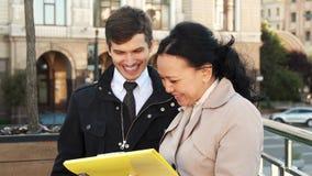 Приятные человек и женщина обсуждают некоторые документы и усмехаются стоковое фото
