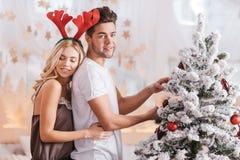 Приятный молодой человек украшая рождественскую елку Стоковое фото RF