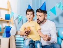Приятный отец помогая маленькому сыну дует вне свеча дня рождения Стоковое фото RF