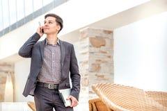 Приятный переговор! Молодой бизнесмен стоя и говоря дальше Стоковые Изображения RF