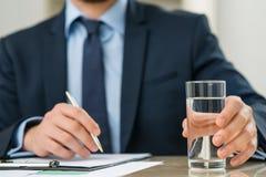 Приятный работник офиса держа стекло воды Стоковые Фото