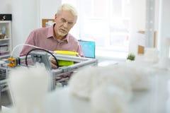 Приятный старший человек хотеть заменить нить в принтере 3D стоковое изображение