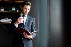 Приятный уверенно щетиненнсяый парень стоит в офисе с кофе Стоковые Изображения RF