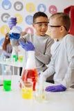 2 приятных одноклассника обсуждая химическую реакцию Стоковое фото RF
