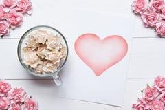 Придайте форму чашки вполне белых роз и бумажный лист с символом сердца дальше сватает Стоковые Фото