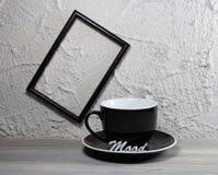 Придайте форму чашки черная опорожните с настроением надписи и photoframe Стоковые Фотографии RF