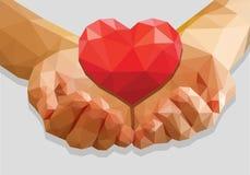 Приданные форму чашки руки держат полигон красного сердца низко-поли на сером цвете Стоковое Изображение RF