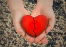 Приданные форму чашки руки держа разбитый сердце Стоковые Фотографии RF