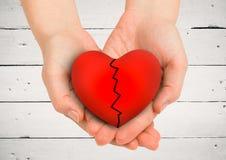 Приданные форму чашки руки держа разбитый сердце Стоковые Фото