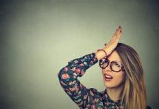 Придурковатая молодая женщина, шлепая руку на голове имея duh момент Сожаления вредят делать стоковое фото