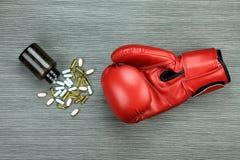 Пробейте прочь болезнь, перчатки бокса и капсулы лекарства стоковые фотографии rf