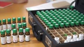 Пробирки на таблице и в чемодане Медицинские сосуды и косметическая ароматность масла сток-видео