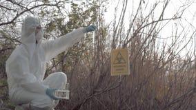 Проблема загрязнения окружающей среды в природе, hazmat в защитные coveralls беря зараженный проба воды в пробирках сток-видео