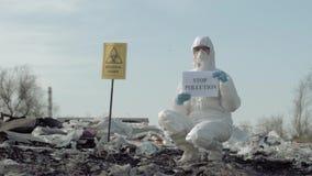 Проблема загрязнения окружающей среды, работник Hazmat в защитную одежду показывает загрязнение стопа знака на хламе для того что сток-видео