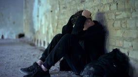 Проблемы отрочества, предназначенный для подростков мальчик пряча в получившемся отказ здании, избежании от задиры стоковое изображение rf
