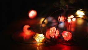 Проблескивая гирлянда рождества лежа на деревянном столе bokeh цветастое рождество предпосылки творческое сток-видео