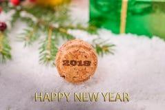 Пробочка от шампанского в снеге на предпосылке украшений и подарков рождества с поздравительным текстом Стоковые Фотографии RF