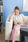 Пробуренная брюзгливая девушка смотря телевидение Стоковые Фото