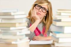 Пробуренная девушка студента между стогом книг Стоковая Фотография RF