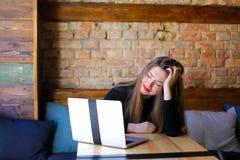 Пробуренная женская персона сидя около современной компьтер-книжки на кафе на софе Стоковые Изображения RF
