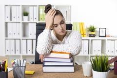 Пробуренная женщина в офисе с гигантскими книгами Стоковые Изображения RF