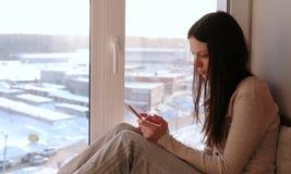 Пробуренная женщина наблюдает что-то на интернете в ее мобильном телефоне пока сидящ на windowsill Стоковая Фотография RF