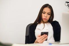 Пробуренная женщина на ее сообщении typimg стола на мобильном телефоне Стоковое Фото