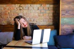 Пробуренная женщина сидя около современной компьтер-книжки на кафе на софе Стоковые Фотографии RF