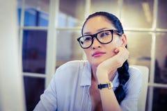Пробуренная женщина сидя на ее столе Стоковые Изображения