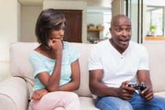 Пробуренная женщина сидя рядом с ее парнем играя видеоигры Стоковые Изображения