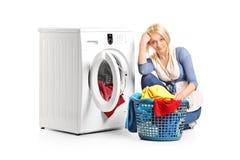 Пробуренная женщина сидя стиральной машиной Стоковая Фотография RF