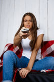 Пробуренная красивая девушка смотря ТВ, сидя на софе дома Стоковые Изображения