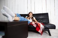 Пробуренная милая девушка смотря ТВ, сидя на софе дома Стоковое Изображение RF