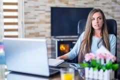 Пробуренная молодая женщина в офисе работая с ноутбуком стоковое фото rf