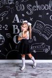 Пробуренная школьница стоя перед доской как предпосылка Изображение портрета стоковая фотография