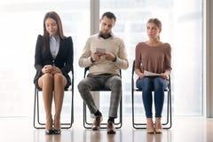 Пробуренные люди сидя на стульях ждать в течение длительного времени Стоковые Фотографии RF