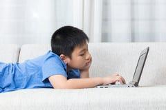 Пробуренный азиатский китайский мальчик используя компьтер-книжку на софе Стоковые Фотографии RF