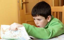 Пробуренный и утомленный мальчик делая домашнюю работу Стоковые Изображения