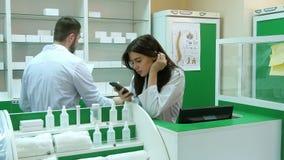 Пробуренный молодой аптекарь broqsing через мобильный телефон на месте работы сток-видео