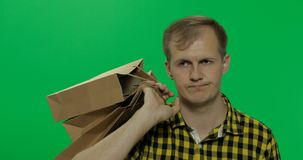 Пробуренный молодой человек на предпосылке зеленого chroma экрана ключевой с хозяйственными сумками стоковое фото
